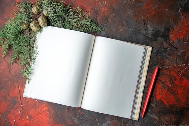 Half schot van open spiraalvormig notitieboekje met rode pen en dennentakken op donkere achtergrond