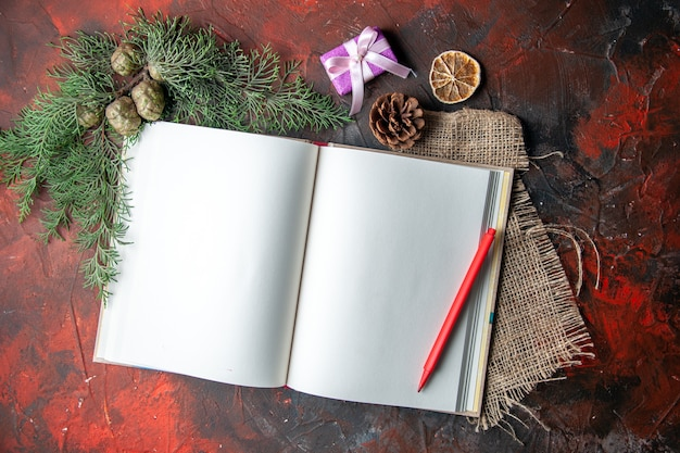 Half schot van open spiraalvormig notitieboekje met rode pen en dennentakken op handdoek op donkere achtergrond