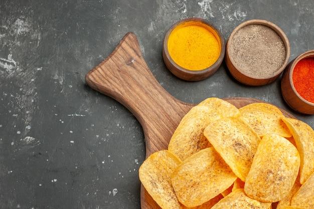 Half schot van smakelijke chips kruiden met ketchup op grijze tafel