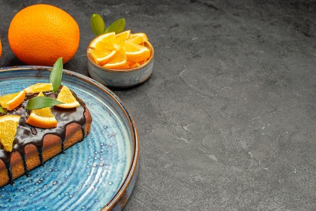 Half schot van zachte heerlijke cake op dienblad en sinaasappel op zwarte lijst