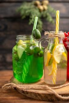 Half shot biologische vruchtensappen in flesjes geserveerd met kokers op een houten snijplank