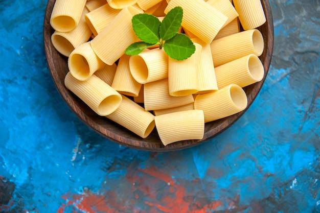Half shot dinerbereiding met pastanoedels met groen in een bruine pot op blauwe achtergrond pot