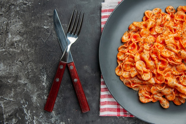 Half shot eenvoudige pastamaaltijd voor het avondeten op een zwart bord en een bestekset