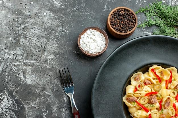 Half shot heerlijke conchiglie met groenten en greens op een bord en mes en verschillende kruiden op grijze achtergrond