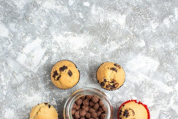 Half shot heerlijke kleine cupcakes en chocolade in een glazen pot naast kerstcadeau op ijstafel