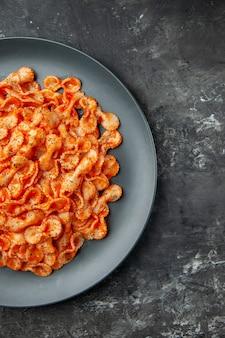 Half shot heerlijke pastamaaltijd op een zwarte plaat voor het diner aan de rechterkant op donkere achtergrond