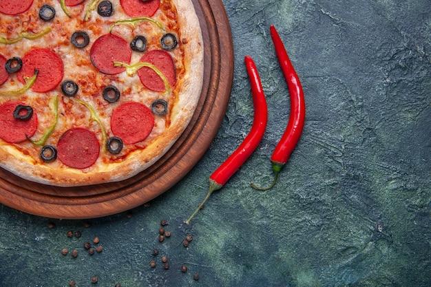 Half shot heerlijke pizza op houten snijplank en rode paprika's op geïsoleerde donkere ondergrond met vrije ruimte