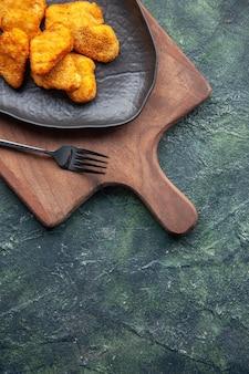 Half shot kipnuggets op een zwarte plaat en vork op houten snijplank aan de rechterkant op donkere ondergrond met vrije ruimte