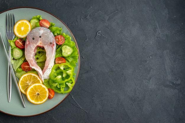 Half shot rauwe vis en verse groenten, schijfjes citroen en bestek op een grijze plaat aan de linkerkant op een zwarte ondergrond met vrije ruimte