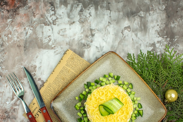 Half shot smakelijke salade geserveerd met gehakte komkommer en mesvork op een oude krant