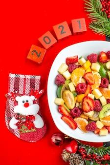 Half shot van de collectie van vers fruit op de accessoires van de dinerbord decoratie dennentakken en cijfers en kerst sok op een rood servet