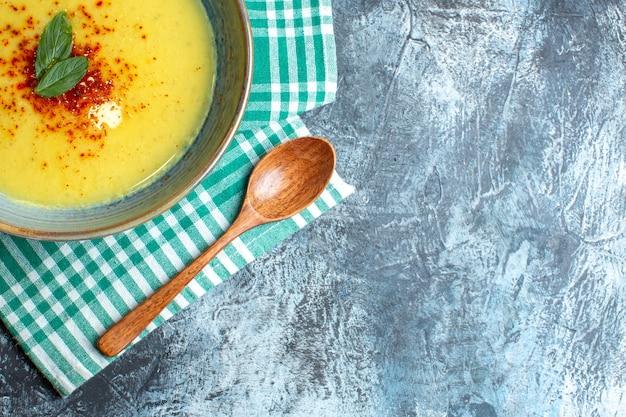 Half shot van een blauwe pot met smakelijke soep geserveerd met munt en houten lepel op groene gestripte handdoek op blauwe achtergrond