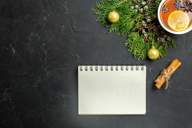 Half shot van een kopje zwarte thee kerstaccessoires en kaneellimoenen en notitieboekje op zwarte achtergrond