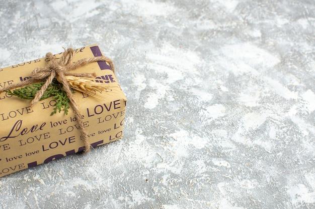 Half shot van een prachtig kerstcadeau met liefdesinscriptie aan de linkerkant op ijstafel