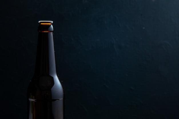Half shot van glazen fles staande op tafel aan de rechterkant op zwarte achtergrond met vrije ruimte