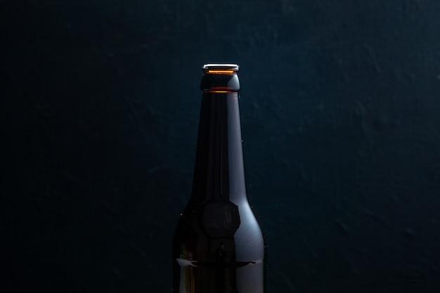 Half shot van glazen fles staande op tafel op zwarte achtergrond met vrije ruimte in vooraanzicht