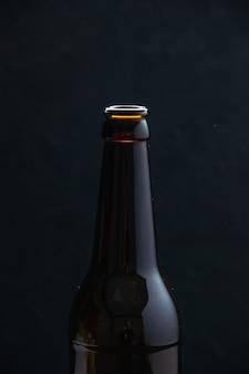 Half shot van glazen fles staande op tafel op zwarte achtergrond met vrije ruimte