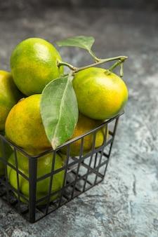 Half shot van groene mandarijnen met bladeren in een mand op grijze achtergrond