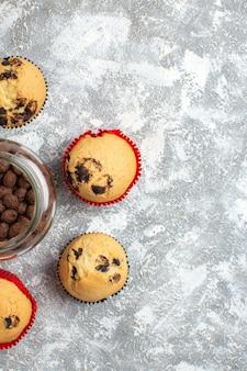 Half shot van heerlijke kleine cupcakes en chocolade in een glazen pot naast kerstcadeau aan de rechterkant op ijstafel in verticale weergave