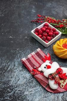 Half shot van heerlijke koekjesdecoratie-accessoire santa claus sok en cornell in een kom dennentakken op een donkere ondergrond