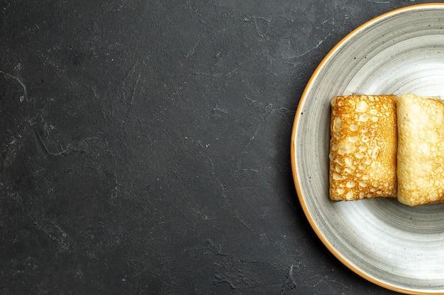 Half shot van heerlijke met vlees gevulde pannenkoeken op een witte plaat op zwarte achtergrond