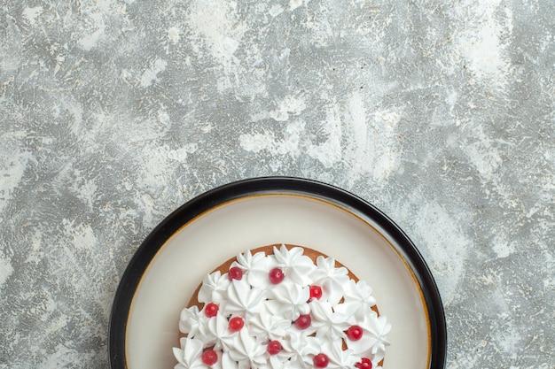 Half shot van heerlijke romige cake versierd met fruit op ijsachtergrond