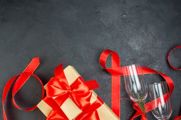 Half shot van mooie geschenken en glazen bekers op donkere achtergrond