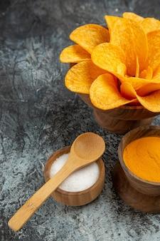 Half shot van smakelijke aardappelchips versierd als bloemvormige verschillende kruiden met lepels erop aan de linkerkant van de grijze tafel