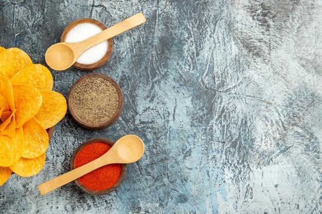 Half shot van smakelijke aardappelchips versierd als bloemvormige verschillende kruiden met lepels erop op grijze tafel