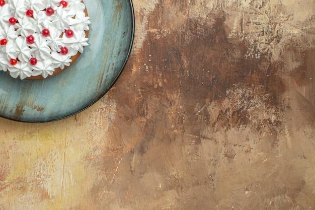 Half shot van smakelijke cake versierd met room en bessen op een blauw bord aan de rechterkant op een kleurrijke achtergrond