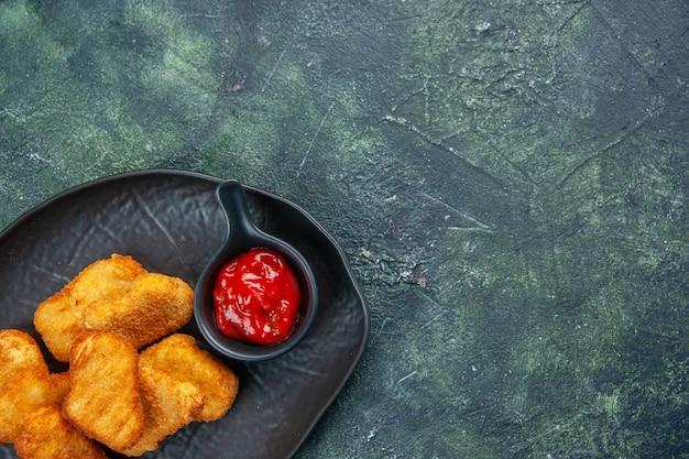 Half shot van smakelijke kipnuggets en ketchup in zwarte borden op een donkere ondergrond met vrije ruimte