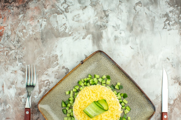 Half shot van smakelijke salade geserveerd met gehakte komkommer en mesvork op gemengde kleurenachtergrond
