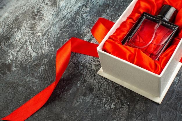 Half shot van vrouwenparfum op een geschenkdoos op rood lint op ijzig
