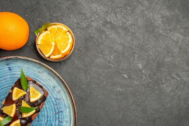 Half shot van zachte heerlijke cake en sinaasappel op zwarte tafel horizontale weergave