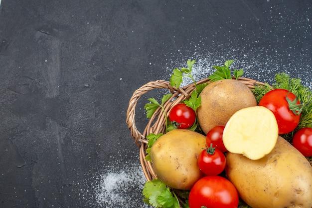 Half shot verse rode tomaten en hele gehakte aardappelkruiden op een gestripte handdoek aan de linkerkant op een donkere achtergrond