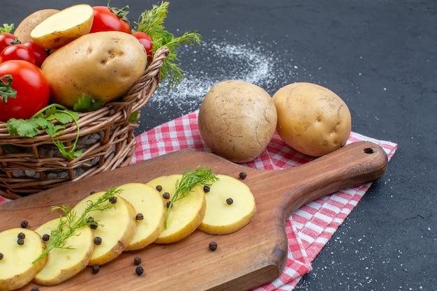 Half shot verse rode tomaten en hele gesneden aardappelen kruiden groen op gestripte handdoek op donkere kleur achtergrond