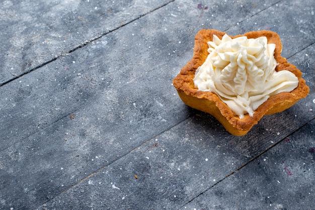 Half-top nauwe weergave heerlijke gebakken cake stervormig met witte lekkere room binnen op licht bureau, cake bak suiker zoete cream tea