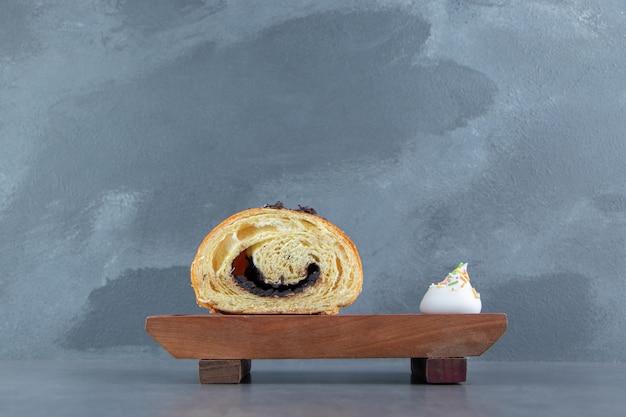 Halfgesneden croissant met chocolade op een houten bord.