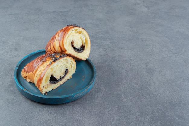 Halfgesneden croissants met chocolade op blauw bord.