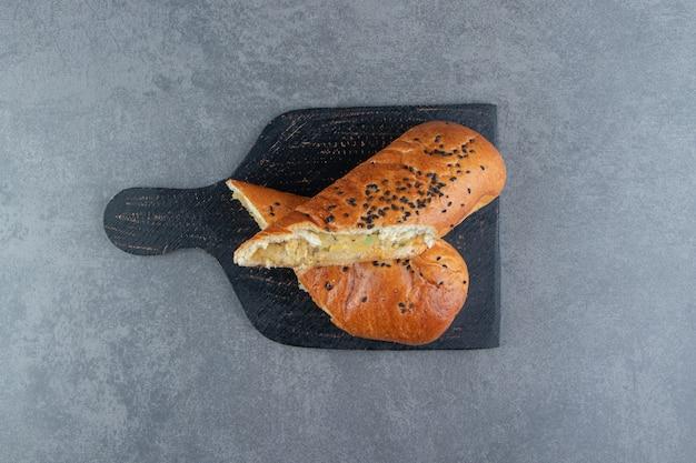 Halfgesneden vers gebak met sesamzaadjes op een zwart bord.