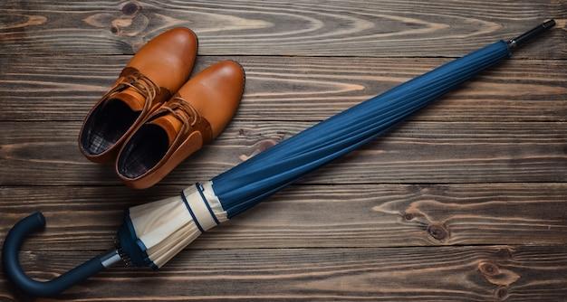 Halfhoge leren halfhoge laarzen en een opgevouwen paraplu op een houten vloer. bovenaanzicht damesaccessoires waxen voor regenachtig weer.
