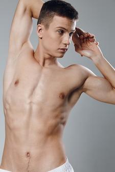 Halfnaakte atleet houdt zijn handen achter zijn hoofd opgepompte spieren druk op bodybuilder