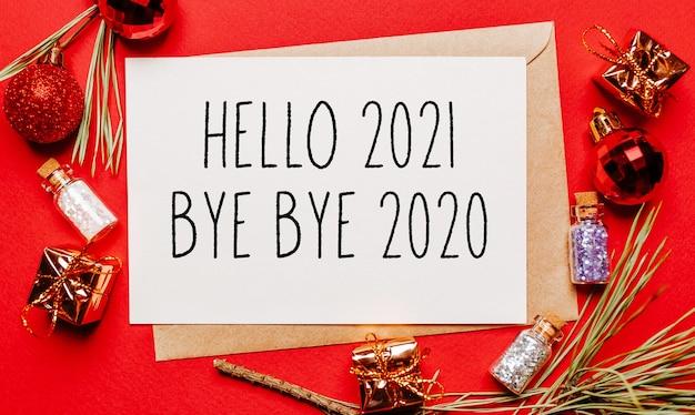 Hallo 2021 bye bye 2020 kerstnota met cadeau, dennentak en speelgoed op rood geïsoleerd. nieuwjaar concept