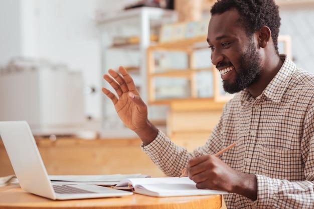 Hallo daar. charmante vrolijke man die aan de tafel in het koffiehuis zit, wat aantekeningen maakt en iemand begroet tijdens een videogesprek