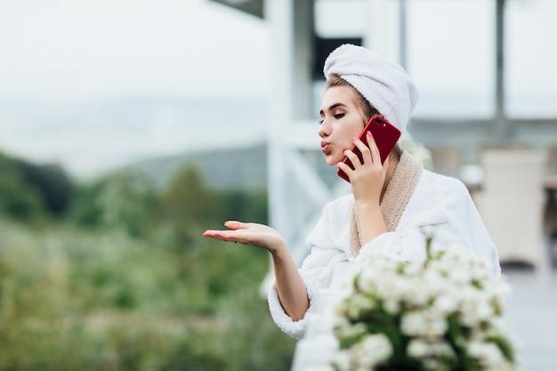 Hallo echtgenoot. jong meisje met telefoonvergadering, kus haar man op het zomerterras op een luxe plek.