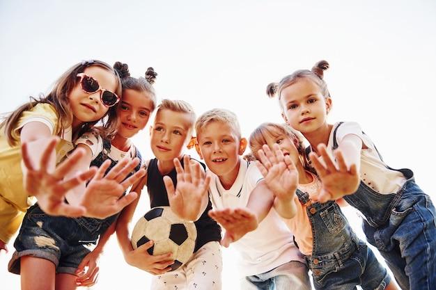 Hallo, gebaar. met voetbal. portret van kinderen die samen staan en poseren voor de camera.