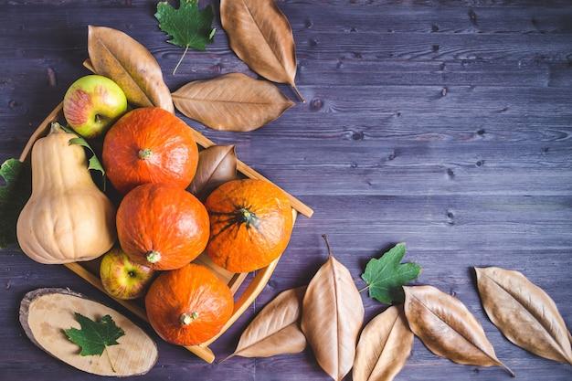 Hallo herfst. oranje pompoenen appels herfst gebladerte op een houten achtergrond
