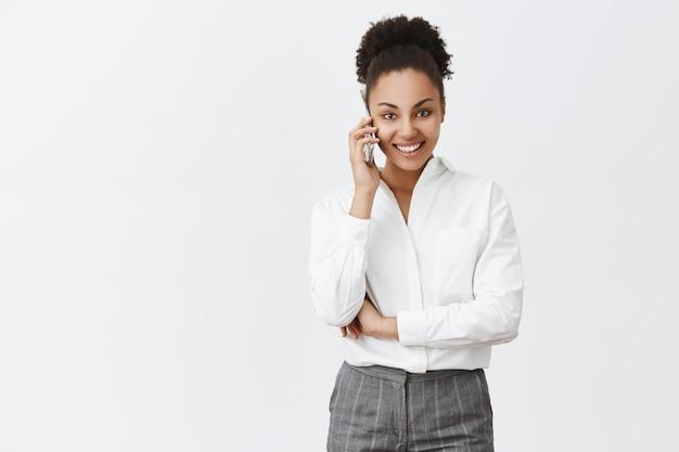 Hallo hoe gaat het. portret van charmante zelfverzekerde zakenvrouw met donkere huid in pak, smartphone in de buurt van oor houden en met zelfverzekerde glimlach staren, afspraak maken over grijze muur