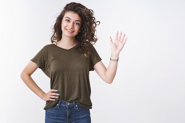 Hallo hoe is het. vriendelijke charmante jonge armeense vrouwelijke collega die je groet met opgeheven hand glimlachend breed kantelend hoofd zeg hallo verwelkomend teamlid, staande witte achtergrond