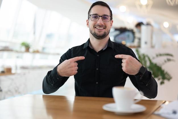 Hallo, ik ben het! aantrekkelijke vrolijke man in zwart shirt wijsvingers op zijn borst en glimlachen. hij zit in een koffiehuis en wacht op een ontmoeting met online vrienden.